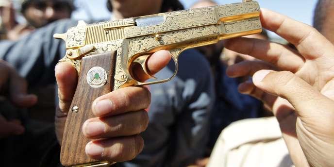 Des combattants du CNT exhibent un pistolet qui aurait appartenu à Mouammar Kadhafi.