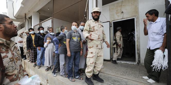 Des Libyens attendent devant la morgue de Misrata pour voir le corps de Mouammar Kadhafi, le 22 octobre 2011.
