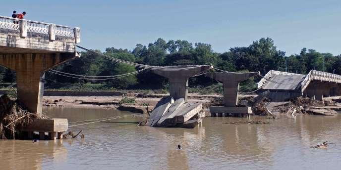 Lors de la précédente inondation en 2011, des Birmans inspectent les dégâts sur un pont emporté par les crues.