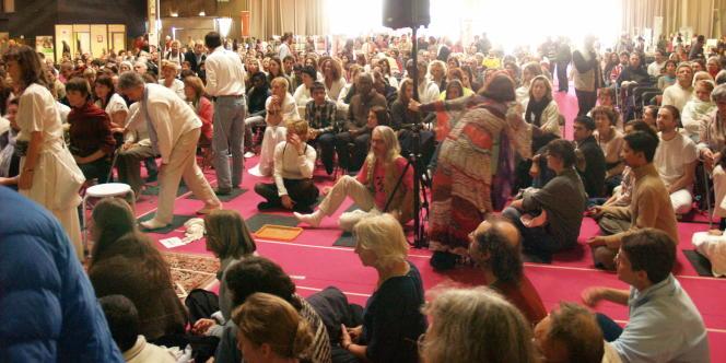 Des centaines de personnes patientent en attendant l'étreinte d'Amma, certains méditent, d'autres s'endorment.