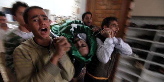 A Homs, le corps d'un manifestant tué par les forces de l'ordre est porté par ses camarades, dans une salle de prière, le 30 octobre.