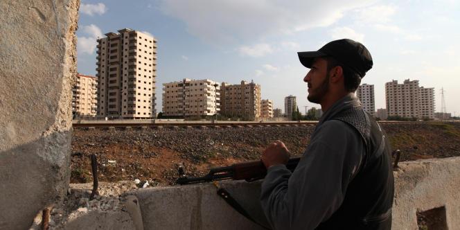 Dans le quartier de Bab Amro, à Homs, un homme de l'Armée syrienne libre surveille les tours où se cachent des snippers des forces de sécurité, le 27 octobre.