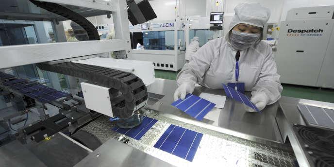 Une ouvrière inspectant des cellules photovoltaïques dans une usine à Hefei (province d'Anhui), le 10 novembre 2011.