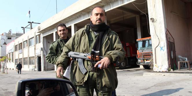 Des membres des forces de sécurité syrienne à l'entrée de Homs, lors d'une visite organisée par le gouvernement, le 24 novembre.
