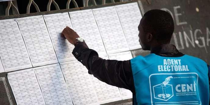 Un agent de la Commission électorale nationale indépendante (CENI) devant un bureau de vote à Lubumbashi, lundi 28 novembre.