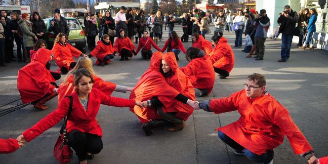 Des manifestants roumains forment un ruban rouge lors d'une flash-mob organisée à Bucarest, le 29 novembre 2011.