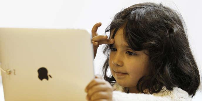 Une petite fille utilise une tablette Apple.