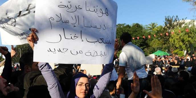''Nous sommes arabes, notre religion est l'islam, le peuple tunisien a choisi Ennahda'', dit la pancarte de cette manifestante, à Tunis, samedi 3 décembre.