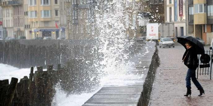 Une femme regarde les vagues s'écraser sur les alignements de poteaux de la plage du Sillon, à Saint-Malo, le 15 décembre 2011.