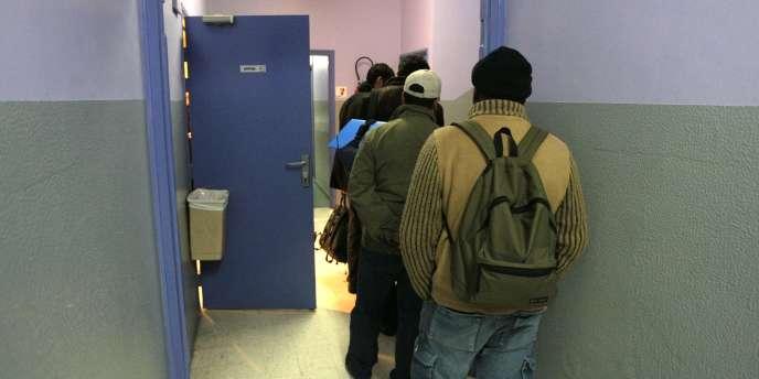 Des sans-abri arrivent, fin 2008, dans un gymnase mis à leur disposition par la Ville de Paris.