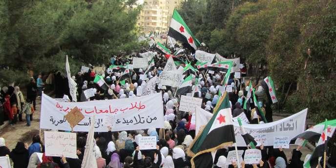 Des manifestants défilent dans les rues de Homs le 13 décembre.