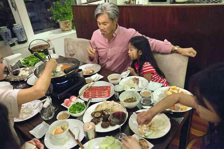 """à New York, Todd Leong partage une fondue avec ses enfants. Pour sa compagne (hors champ), """" ce qui est amusant, avec ce plat,  c'est que chacun trempe ce qu'il veut dans le bouillon """". - PHOTO : Stéphanie Sinclair/VII"""