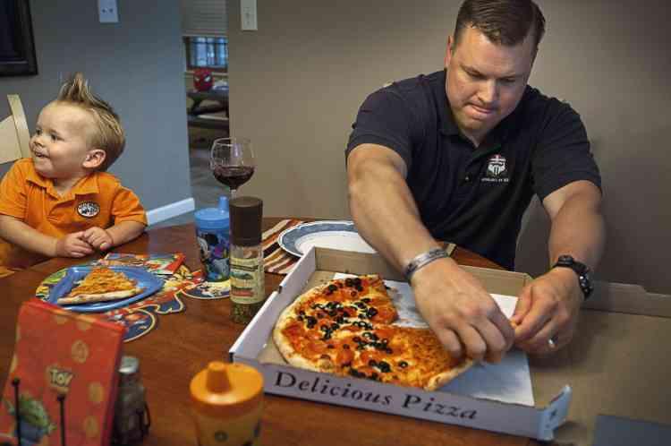 """Sur la base militaire de Fort Dix, dans le New Jersey, le sergent Jeff Glitzow s'attable avec son son fils Dylan. """" La pizza du vendredi soir, c'est une tradition depuis que je suis gamin, dit-il,  et je l'ai poursuivie après mon mariage. """" - PHOTO : Stéphanie Sinclair/VII"""