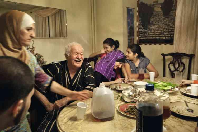 """la famille Sarsour, à Brooklyn, d'origine palestinienne, est réunie autour des grands-parents Maha et Nidal. Leur fille Linda (avec le foulard violet) explique : """" Ma mère pense que manger la cuisine traditionnelle entretient le lien  avec notre culture. """" - PHOTO : Stéphanie Sinclair/VII"""
