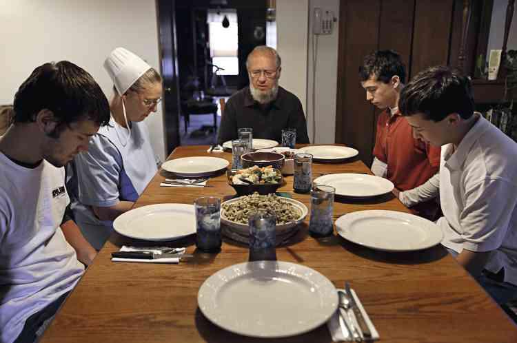 """A Berlin, dans l'Ohio,  la famille Schlabach, membre d'une communauté amish, prie avant le repas. """" Après le repas, explique Mary Ann, la mère, nous lisons la Bible. Ce qui donne parfois lieu à une bonne discussion. """" - PHOTO : Stéphanie Sinclair/VII"""