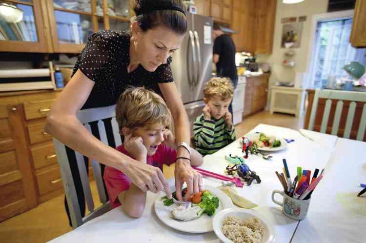 """à Brooklyn, Leslie Astor fait manger ses deux fils tandis que son mari, Harry, s'active en cuisine. """" Souvent le cadet lance de la nourriture à son grand frère """", témoigne le papa. - PHOTO : Stéphanie Sinclair/VII"""