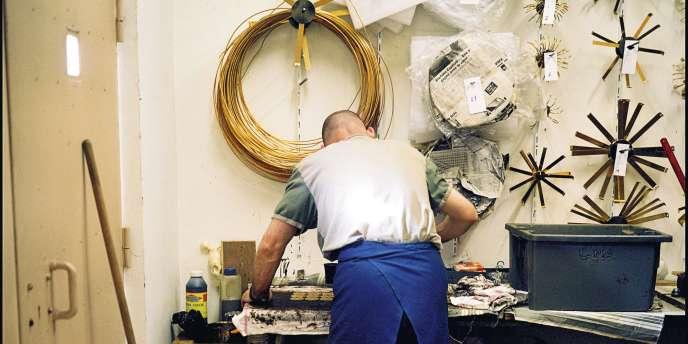 A la maison d'arrêt de Poissy  (Yvelines), un -prisonnier travaille pour une entreprise de fabrication de lustres.