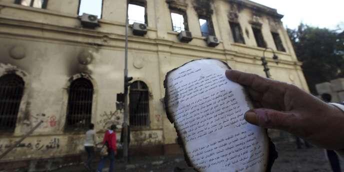 Des manifestants ont pénétré, dimanche 18 décembre, dans le bâtiment encore fumant de l'Institut d'Egypte, incendié la veille, pour en extraire des manuscrits anciens, dont une partie était brûlée.