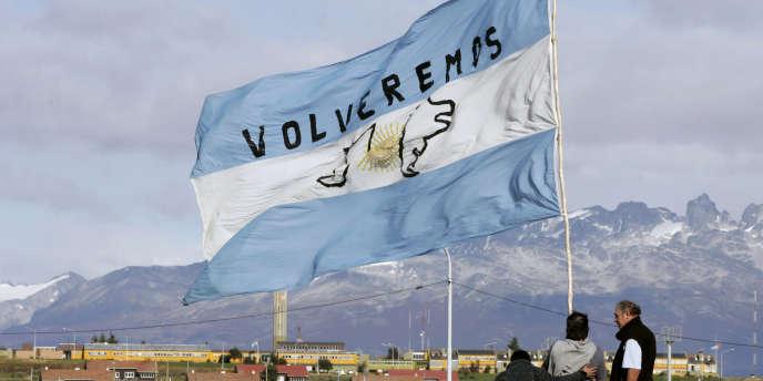 Des Argentins brandissent un drapeau sur lequel est écrit