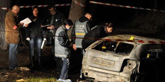 Des enquêteurs de la police judiciaire et des membres de la police technique et scientifique procèdent aux premières investigations sur un véhicule calciné où trois corps calcinés ont été retrouvés, le 26 décembre 2011 aux Pennes-Mirabeau.
