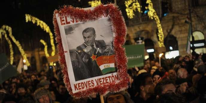 Des manifestants arborent un portrait du premier ministre hongrois, Viktor Orban, dépeint en dictateur de l'ère communiste, le 2 janvier à Budapest.
