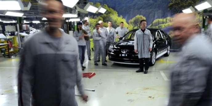 Des ouvriers de l'usine PSA de Sochaux sont rassemblés autour de la dernière Peugeot 607 produite ce jour dans l'usine, le 4 mars 2009.