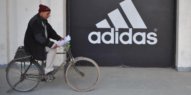 Un cycliste devant un magasin Adidas, à New Delhi, le 11 janvier 2012.