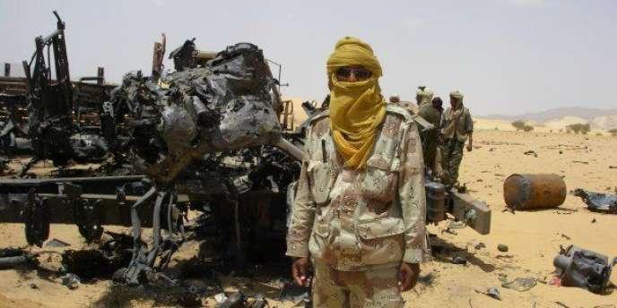 Un Touareg pose devant une carcasse d'avion. Le MNLA affirme avoir abattu un MIG-21 malien.