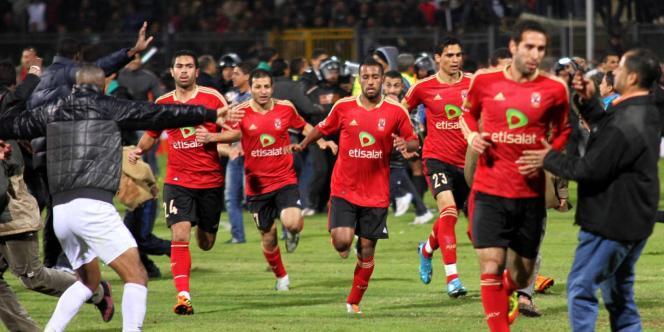 Des joueurs du club égyptien Al-Ahly courent pour se mettre à l'abri après que des supporteurs du club adverse ont envahi le terrain du stade de Port-Saïd, le 1er février.