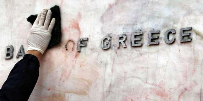 Un employé nettoie la façade de la Banque de Grèce, à Athènes, mardi 14 février.