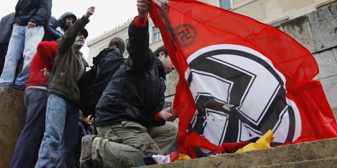 Des Grecs protestent contre l'austérité en brûlant un drapeau allemand et un drapeau nazi devant le Parlement d'Athènes, le 7 février.