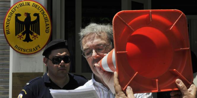 L'avocat allemand Joachim Rollhauser lit une déclaration devant l'ambassade d'Allemagne à Athènes lors d'une manifestation de citoyens allemands réclamant des réparations immédiates pour toutes les victimes grecques du nazisme, le 6 juin 2011.