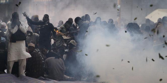 Des Sénégalais priant devant une mosquée en solidarité avec les manifestants de l'opposition sont visés par les gaz lacrymogènes, le 17 février.