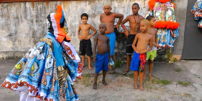 Regards d'envie sur un enfant du quartier dont les parents ont réussi à lui offrir son costume... Ultimes préparatifs avant la sortie du gang de l'Indio, dans le quartier de Guadalupe, zone nord de Rio de Janeiro.