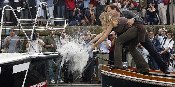 Emmanuelle Béart et Charles Berling brisent une bouteille de champagne sur le voilier de Marc Thiercelin en 2004.
