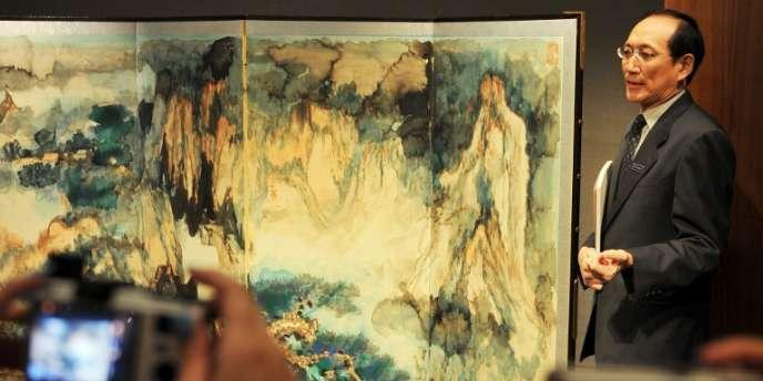 Cheung Chiu-kwan, chef de la section peinture chinoise à Sotheby, montre une oeuvre de Zhang Daqian lors d'une exposition à Hong Kong,