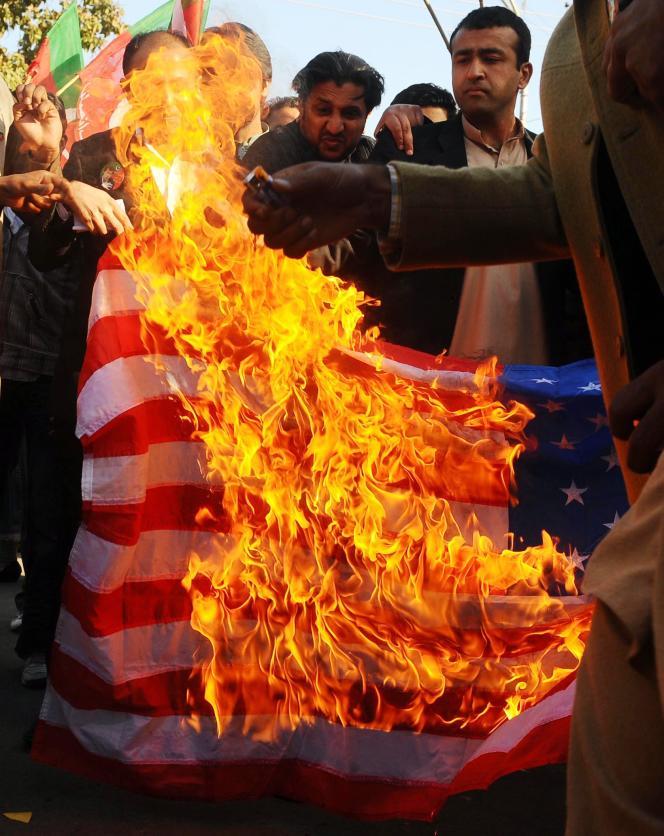 Un drapeau américain en feu à Lahore (est), le 24 février.
