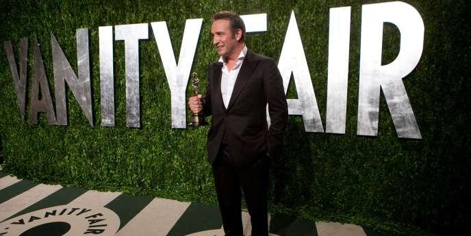 L'acteur Jean Dujardin arrivant avec son Oscar à la fête organisée par
