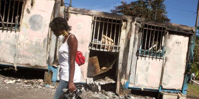 Une femme passe devant un centre social brûlé de Saint-Denis le 23 février, après la deuxième nuit d'émeutes contre la vie chère à la Réunion
