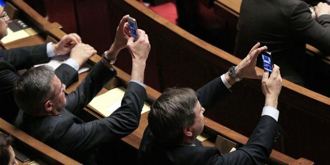 Des députés prennent en photo François Fillon, mardi 6 mars, à l'Assemblée nationale, lors de la dernière séance de la législature.