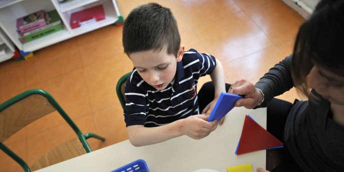 Une éducatrice s'occupe d'un enfant autiste, à l'institut médico-éducatif