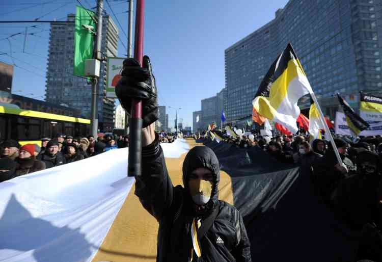 Nationalists carry the black-yellow-white flags of the Russian Empire as they take part in anti-Putin rally in the central Arbat area in Moscow, on March 10, 2012. Russia's protest movement against Vladimir Putin rallied today several thousand people for a new demonstration that is a test of their strength and tactics after his crushing election victory.  AFP PHOTO / NATALIA KOLESNIKOVA
