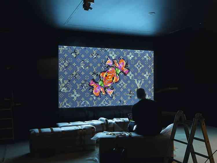 En guise de transition (en haut) entre l'univers de Louis Vuitton et celui de Marc Jacobs, une vidéo de l'artiste Jonathan Lu joue avec le graphisme des différents monogrammes, dont ceux  réinterprétés par Takashi Murakami ou Richard Prince. Ici, celui de  Stephen Sprouse, dont  la rose orna certaines pièces de la collection printemps-été 2001. -
