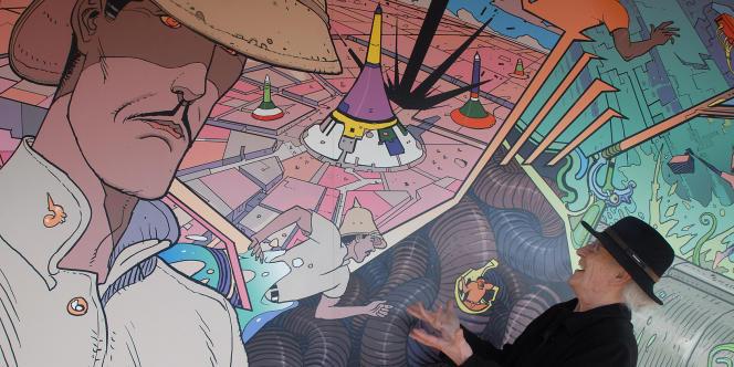Jean Giraud alias Moebius pose devant une fresque tirée d'un de ses albums, le 9 février 2008 au Futuroscope de Poitiers, le jour du lancement d'une nouvelle attraction du parc, inspirée de l'un de ses albums.