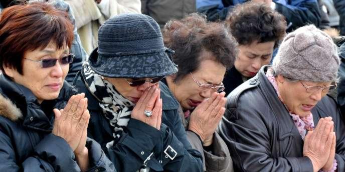 Commémoration du premier anniversaire du tsunami devant une école élémentaire à Ishinomaki, le 11 mars 2012.