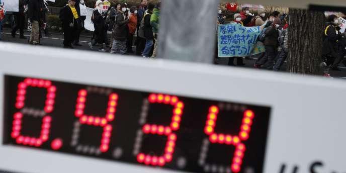 Défilé en mémoire des victimes des catastrophes du 11 mars 2011 à Koriyama, dans la préfecture de Fukushima, le 11 mars 2012. Un panneau indique le taux de radioactivité : 0,434 microsievert/heure.