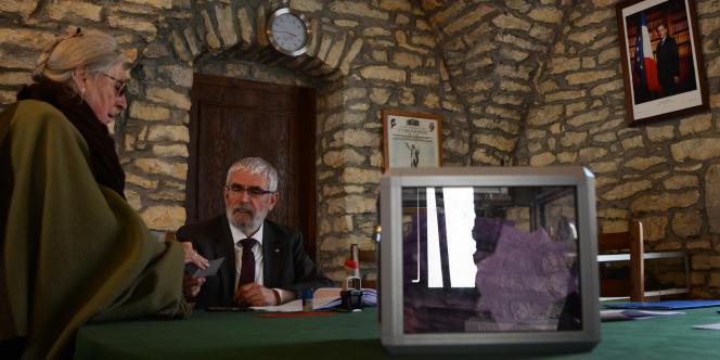 Dimanche, à la mairie de Saint-Julien, le maire Gérard Guyot fait émarger les habitants lors du vote de consultation.