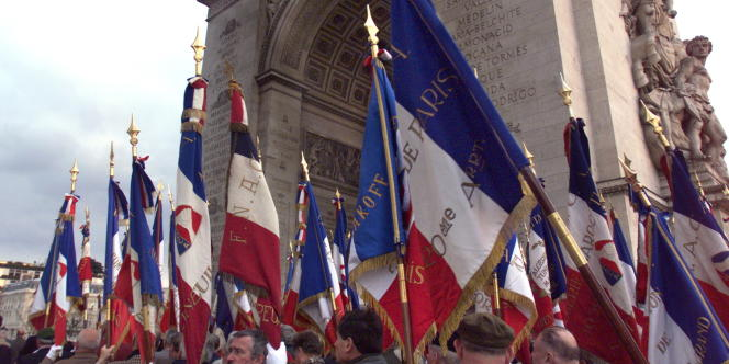 Des adhérents à la Fnaca portant des drapeaux tricolores, assistent, le 19 mars 1999 à Paris, devant la tombe du soldat inconnu, à la cérémonie de commémoration du 37e anniversaire du cessez-le-feu qui avait mis fin officiellement le 19 mars 1962 à la guerre d'Algérie.