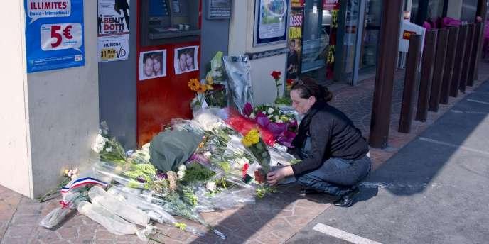 Une femme dépose un bouquet à Montauban, le 15 mars 2012.