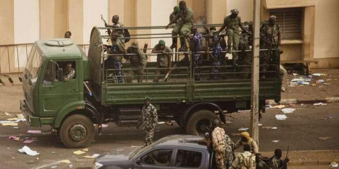 Des militaires maliens en poste devant le siège de la radio-télévision publique à Bamako, jeudi 22 mars.